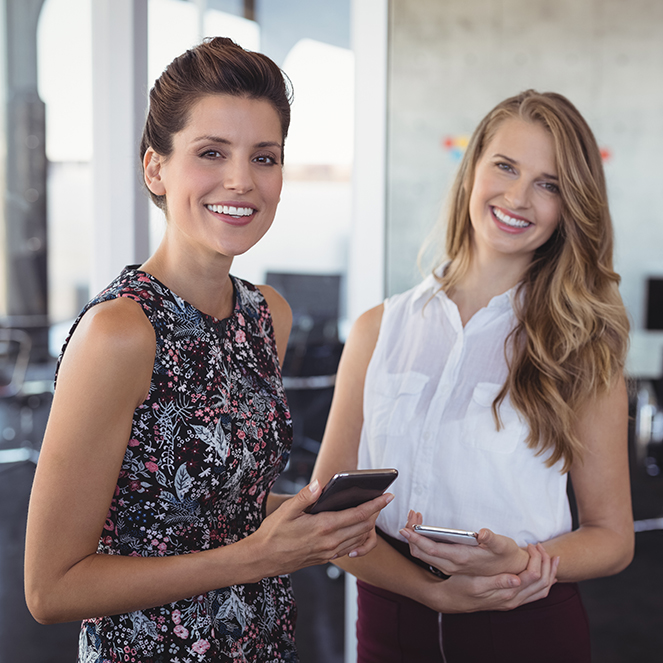Portrait of smiling female colleagues holding mobile phones while standing at creative office